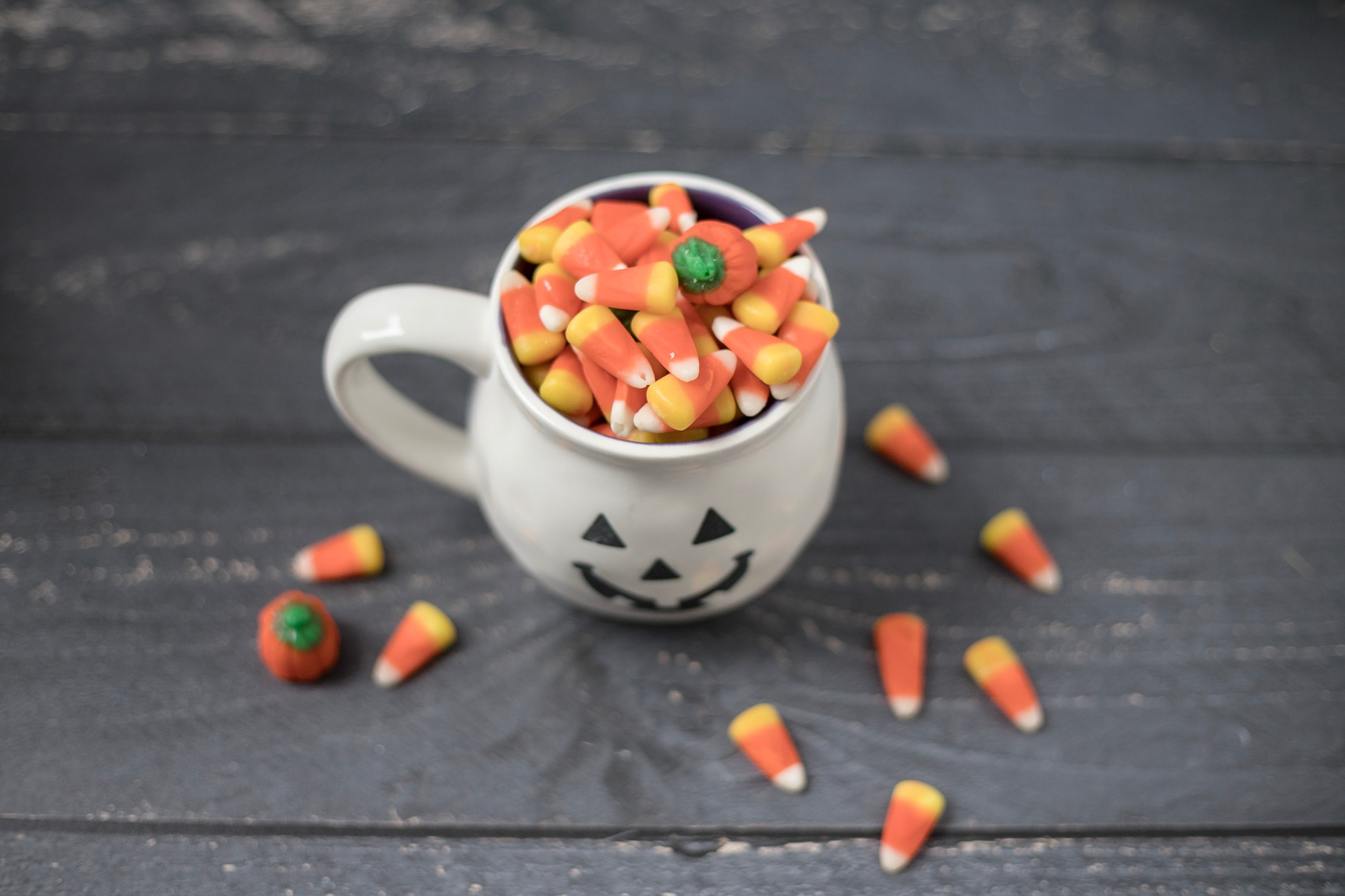 Halloween themed pumpkin shaped mug filled with candy corn