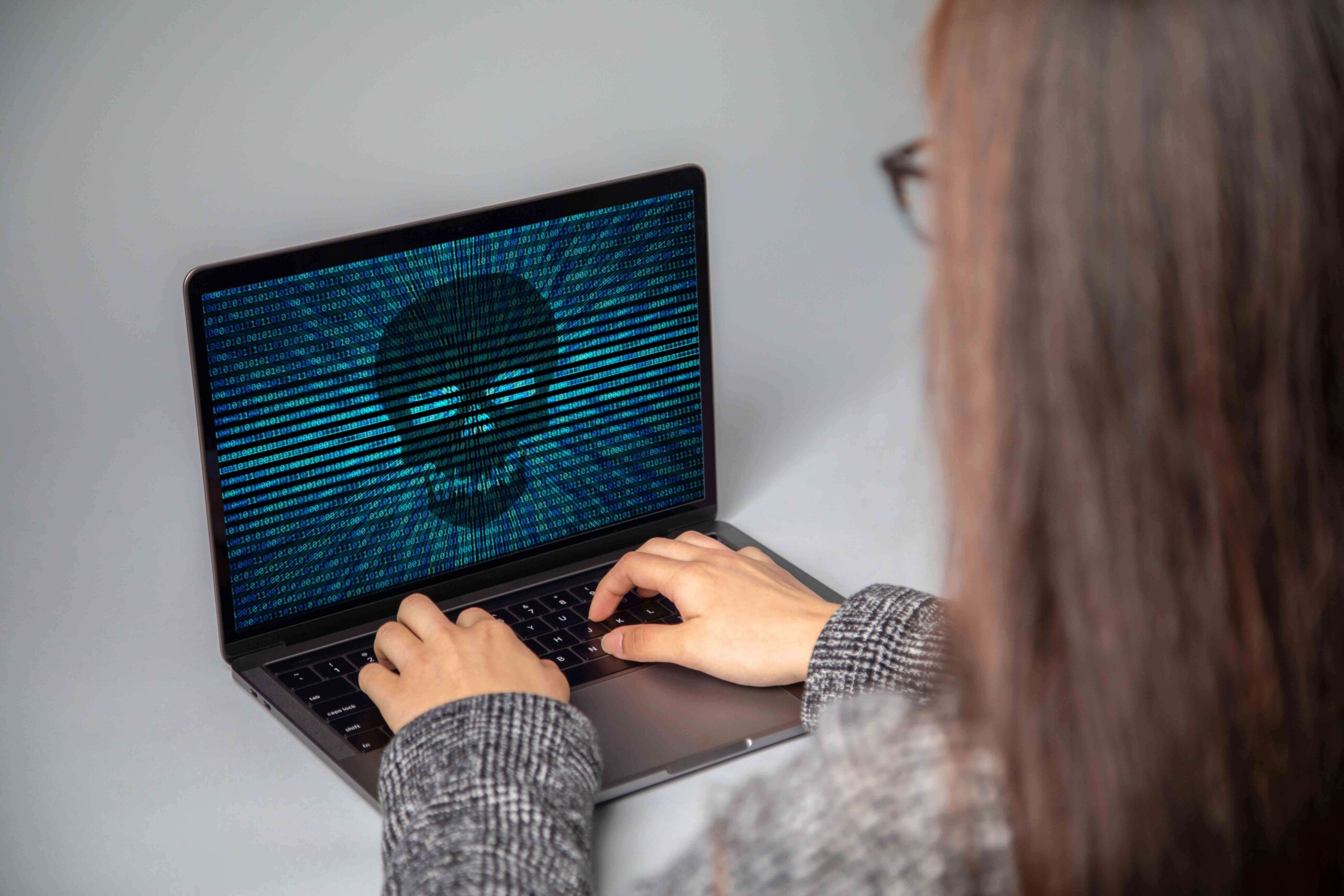 Woman using computer with security alert on screen