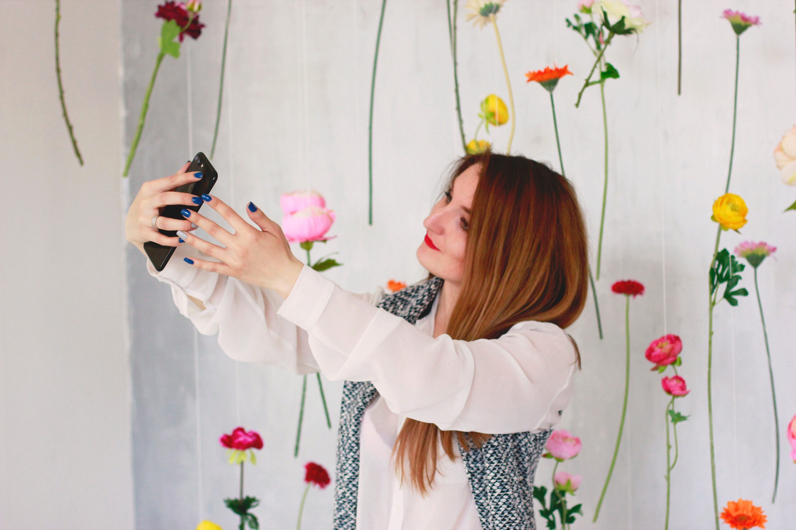 Young girl taking a selfie in front of a decorated wall.