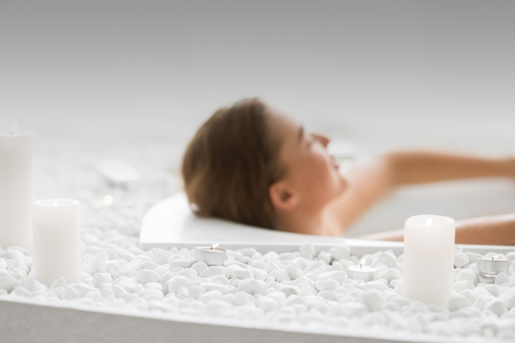 Woman reclines in a bathtub with candles nearby