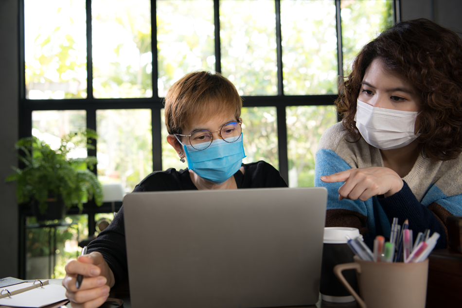 2 people in masks at a computer