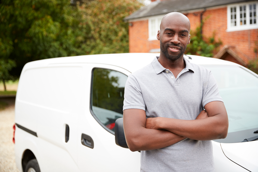a man standing by his vehicle smiling